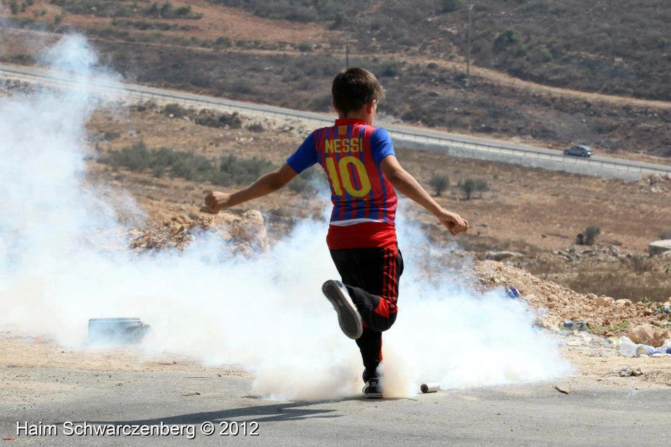 shaker's son ahmad kicking away a tear gas canister